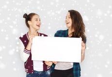Smiling teenage girls holding white blank board Stock Photos