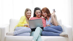 Smiling teenage girls with laptop and credit card Royalty Free Stock Image