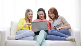 Smiling teenage girls with laptop and credit card stock video footage