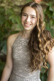 Smiling teenage girls with long brown hair and taupe dress. Royalty Free Stock Photo