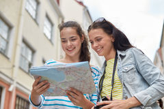 Smiling teenage girls with map and camera outdoors Royalty Free Stock Photography