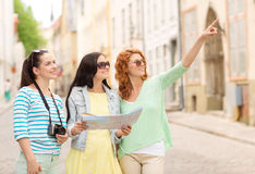 Smiling teenage girls with map and camera Stock Photography
