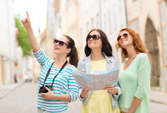 Smiling teenage girls with map and camera Stock Photos