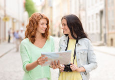 Smiling teenage girls with map and camera Royalty Free Stock Images