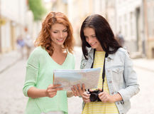 Smiling teenage girls with map and camera Royalty Free Stock Image
