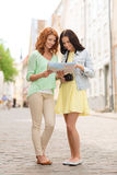 Smiling teenage girls with map and camera Royalty Free Stock Photography