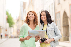 Smiling teenage girls with map and camera Stock Images