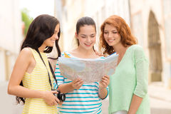 Smiling teenage girls with map and camera stock photo