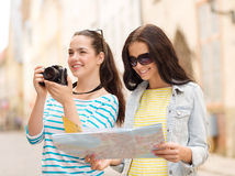 Smiling teenage girls with map Royalty Free Stock Photo