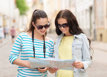 Smiling teenage girls with map Royalty Free Stock Photography