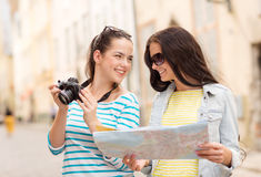 Smiling teenage girls with map Royalty Free Stock Images