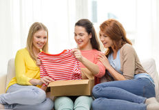 Smiling teenage girls opening cardboard box. Transportation, post and friendship concept - three smiling teenage girls opening cardboard box at home Stock Photos