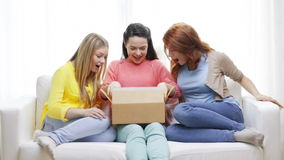Smiling teenage girls opening cardboard box stock footage