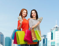 Smiling teenage girls with shopping bags and money Stock Photography