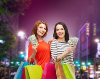 Smiling teenage girls with shopping bags and money Stock Images