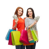 Smiling teenage girls with shopping bags and money Stock Photo