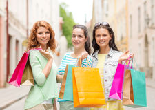 Smiling teenage girls with shopping bags on street Royalty Free Stock Photo