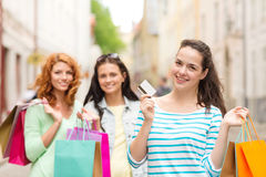 Smiling teenage girls with shopping bags on street Stock Photo
