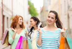 Smiling teenage girls with shopping bags on street Stock Image