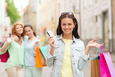 Smiling teenage girls with shopping bags on street Stock Photos