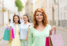 Smiling teenage girls with shopping bags on street Stock Images