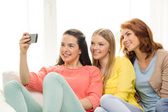 Smiling teenage girls with smartphone at home Stock Photos