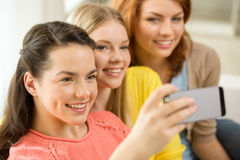 Smiling teenage girls with smartphone at home Royalty Free Stock Images
