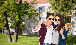 Smiling teenage girls in sunglasses showing peace Royalty Free Stock Photography