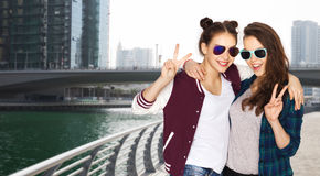 Smiling teenage girls in sunglasses showing peace Stock Image