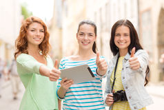 Smiling teenage girls with tablet pc and camera Royalty Free Stock Photo