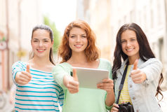 Smiling teenage girls with tablet pc and camera Royalty Free Stock Images