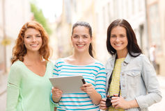 Smiling teenage girls with tablet pc and camera Royalty Free Stock Image