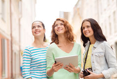 Smiling teenage girls with tablet pc and camera Royalty Free Stock Photography