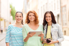 Smiling teenage girls with tablet pc and camera Stock Photo