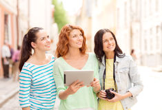 Smiling teenage girls with tablet pc and camera Stock Photos