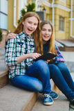 Smiling teenage girls with tablet pc computer outdoors Stock Images
