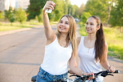 Smiling teenage girls taking self portrait with mobile phone Royalty Free Stock Photos