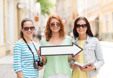 Smiling teenage girls with white arrow outdoors Royalty Free Stock Images