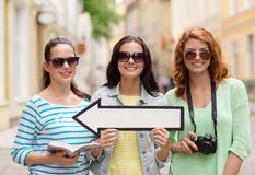 Smiling teenage girls with white arrow outdoors Royalty Free Stock Photo