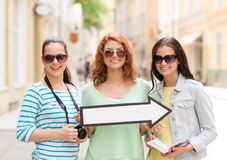 Smiling teenage girls with white arrow outdoors Royalty Free Stock Image