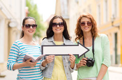 Smiling teenage girls with white arrow outdoors Stock Images
