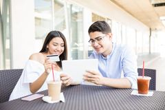 Lovers Shopping Online On Tablet Computer At Mall. Smiling teenage lovers shopping online on tablet computer at mall cafe Royalty Free Stock Photo