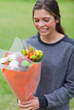 Smiling teenage receiving a bunch of flowers Royalty Free Stock Images