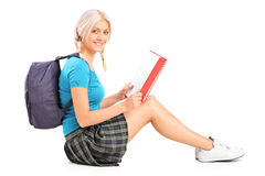 A smiling teenage schoolgirl reading a book Stock Image