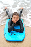 Smiling Teenage Surfer. In a wetsuit laying on his bodyboard on the beach Stock Photo