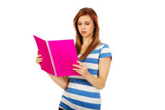 Smiling teenage woman reading her notes Royalty Free Stock Photos