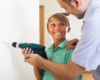 Smiling teenager assist father to using drill Royalty Free Stock Photo