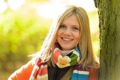 Smiling teenager blonde girl woods tree autumn Royalty Free Stock Image
