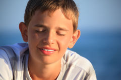Smiling teenager boy against sea, closed eyes Royalty Free Stock Photos