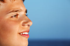 Smiling teenager boy against sea, Looking afar Stock Image